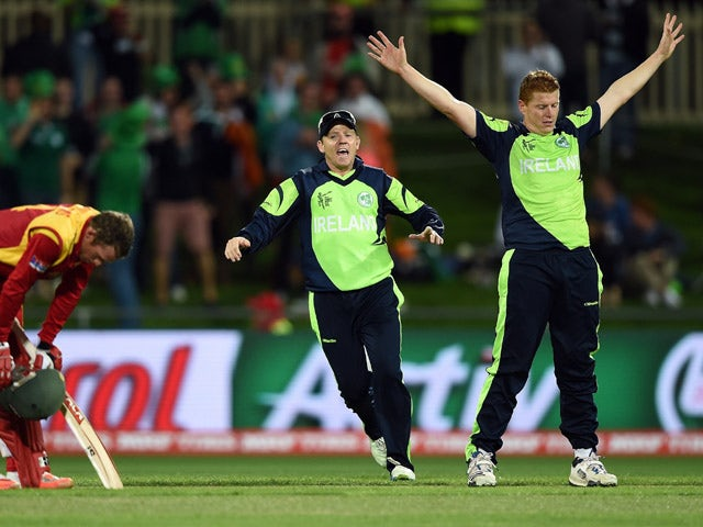 Ireland cricketer Nial O'Brien runs in to congratulate brother and teammate Kevin O'Brien after he took the wicket of Zimbabwe batsman Sean Williams (L) at the Bellerive Oval ground during the 2015 Cricket World Cup Pool B match between Ireland and Zimbab
