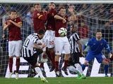 Juventus' Argentine forward Carlos Tevez shoots a free kick and scores a goal during the Italian Serie A football match between AS Roma and Juventus at the Olympic Stadium in Rome on March 2, 2015