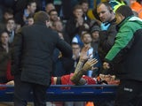 Liverpool's Slovakian defender Martin Skrtel talks with Liverpool's Northern Irish manager Brendan Rodgers as he is carried off the pitch on a stretcher during FA Cup quarter-final match between Liverpool and Blackburn Rovers at Anfield in Liverpool, nort