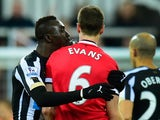 Manchester United player Jonny Evans looks on as Papiss Cisse of Newcastle appears to spit during the Barclays Premier League match between Newcastle United and Manchester United at St James' Park on March 4, 2015