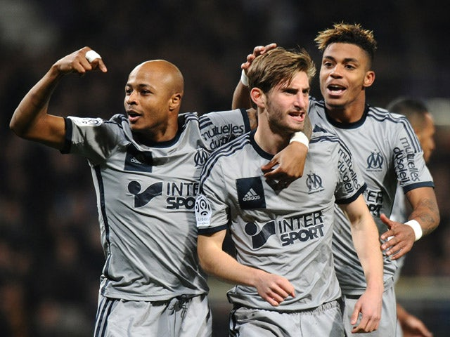 Marseille's French defender Baptiste Aloe celebrates with teammates after scoring a goal during the French L1 football match between Toulouse and Marseille in Toulouse, southwestern France, on March 6, 2015