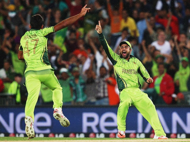 Wahab Riaz of Pakistan celebrates with Ahmad Shahzad of Pakistan after claiming the last wicket of Imran Tahir of South Africa to win the 2015 ICC Cricket World Cup match between South Africa and Pakistan at Eden Park on March 7, 2015