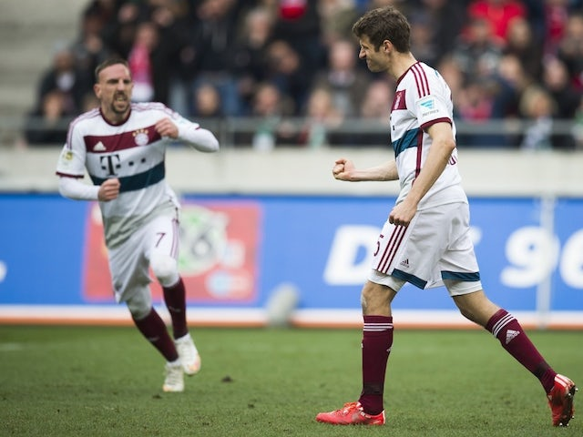 Bayern Munich's forward Thomas Mueller (R) celebrates scoring a penalty goal during the German first division Bundesliga football match against Hanover 96 on March 7, 2015