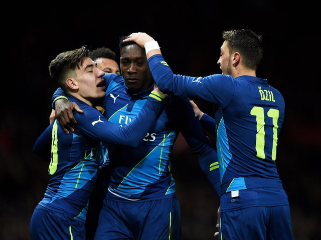 Danny Welbeck of Arsenal celebrates with teammates Hector Bellerin and Mesut Ozil of Arsenal after scoring his team's second goal during the FA Cup Quarter Final match between Manchester United and Arsenal at Old Trafford on March 9, 201