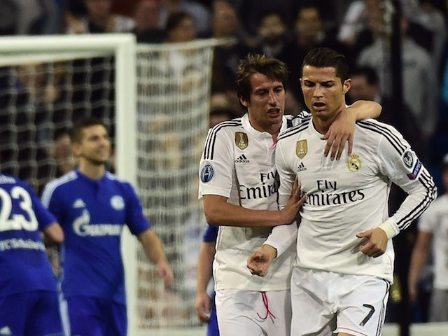 Real Madrid's Portuguese forward Cristiano Ronaldo (R) is congratulated by Fabio Coentrao (C) during the UEFA Champions League round of 16 match against Schalke on March 10, 2015