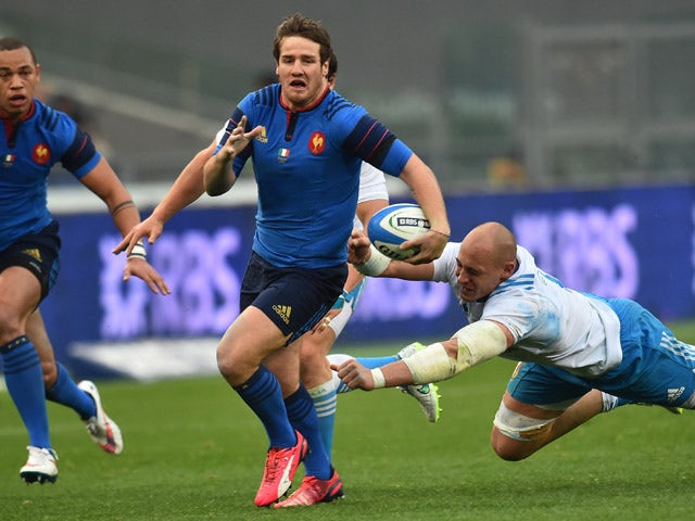France's fly-half Camille Lopez escapes from Italy's Sergio Parisse during the Six Nations international rugby union match between Italy and France on March 15, 2015