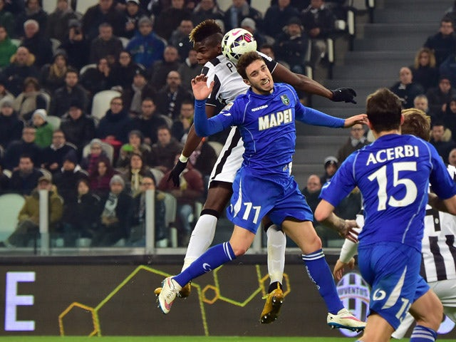 Sassuolo's defender from Croatia Sime Vrsaljko fights for the ball with Juventus' midfielder Paul Pogba during the Serie A football match Juventus vs Sassuolo at 'Juventus Stadium' in Turin on March 09, 2015