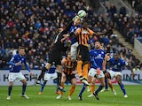 Mark Schwarzer of Leicester City punches the ball clear of Dame N'Doye of Hull and Ritchie De Laet of Leicester City during the Barclays Premier League match between Leicester City and Hull City at The King Power Stadium on March 14, 2015