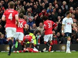 Wayne Rooney of Manchester United is congratulated by teammates after scoring his team's third goal during the Barclays Premier League match between Manchester United and Tottenham Hotspur at Old Trafford on March 15, 2015