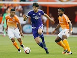 Kaka #10 of the Orlando City SC moves with the ball between Luis Garrido #8 and Jermaine Taylor #4 of the Houston Dynamo during their game at BBVA Compass Stadium on March 13, 2015