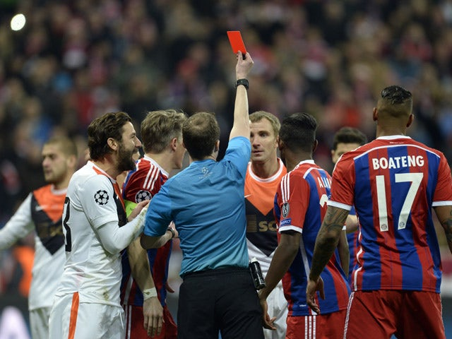 Scottish referee William Collum shows the red card to Shakhtar Donetsk's defender Olexandr Kucher during the UEFA Champions League second-leg round of 16 football match FC Bayern Munich vs Shaktar Donetsk in Munich, southern Germany, on March 11, 2015