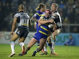 Chris Hill of Warrington Wolves is tackled by Jamie Peacock of Leeds Rhinos during the First Utility Super League match between Warrington Wolves and Leeds Rhinos at The Halliwell Jones Stadium on March 13, 2015