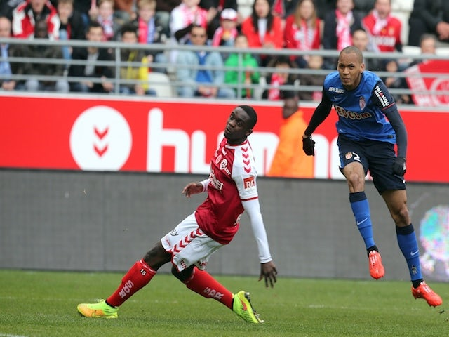 Monaco's defender Fabio Tavares (R) scores a goal next to Reims' Congolese defender Prince Oniangue (L) during the French Football match between Reims and Monaco, on March 22, 2015