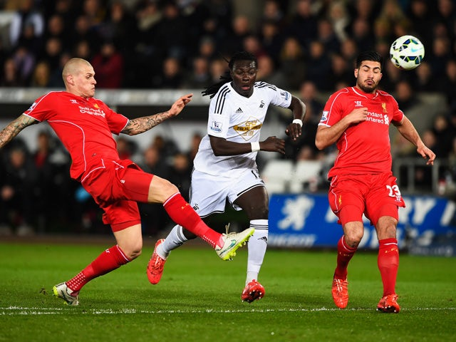 Bafetimbi Gomis of Swansea City is closed down by Martin Skrtel and Emre Can of Liverpool during the Barclays Premier League match between Swansea City and Liverpool at Liberty Stadium on March 16, 2015
