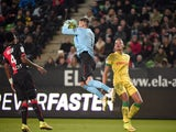 Rennes' French goalkeeper Benoit Costil grabs the ball next to Nantes' French forward Yacine Bammou during the French L1 football match Rennes against Nantes on March 21, 2015
