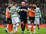 Referee Bobby Madden keeps Kris Commons of Celtic and Ryan McGowan of Dundee United apart during the Scottish League Cup Final between Dundee United and Celtic at Hamden Park on March 15, 2015