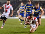 Jon Wilkin of St Helens scores a first half try past Matty Russell of Warrington Wolves during the First Utility Super League match between St Helens and Warrington Wolves at Langtree Park on March 19, 2015