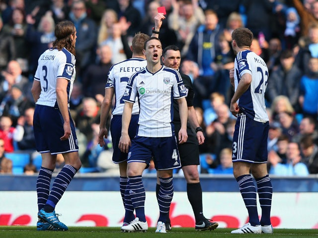 Referee Neil Swarbrick shows Gareth McAuley of West Brom (R) a red card during the Barclays Premier League match between Manchester City and West Bromwich Albion at Etihad Stadium on March 21, 2015