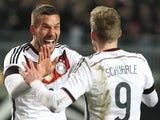 Germany's midfielder Lukas Podolski (L) celebrates scoring the 2-2 goal with midfielder Andre Schuerrle during the friendly football match Germany vs Australia in Kaiserslautern, southern Germany on March 25, 2015