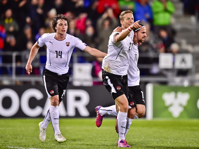 Austria's Marc Janko celebrates with teammates Martin Harnik and Julian Baumgartlinger after scoring the second goal of the match during the Euro 2016 qualifying football match between Liechtenstein and Austria at the Rheinpark stadium in Vaduz on March 2