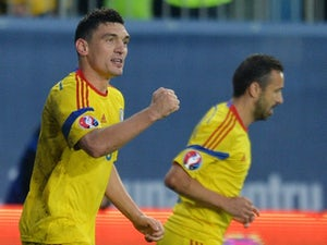 Romania battle to narrow victory