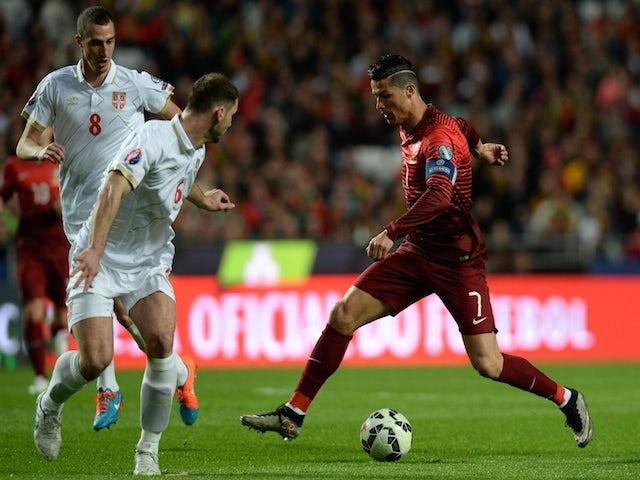 Portugal's forward Cristiano Ronaldo (R) controls the ball near Serbian defender Branislav Ivanovic (C) and midfielder Aleksandar Mitrovic during the Portugal vs Serbia EURO 2016 qualifying football match at Luz stadium in Lisbon on March 29, 2015