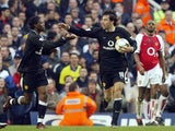 Manchester United's Louis Saha (L) is congratulated by teammate Ruud Van Nistelrooy (C) watched by Arsenal captain Patrick Vieira after scoring an equalizer during their FA Premier League clash at Highbury in London, 28 March 2004