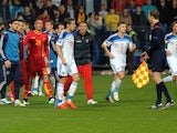 Players leave the pitch as the referee suspends the Euro 2016 group G qualifying football match between Montenegro and Russia at the City stadium in Podgorica on March 27, 2015