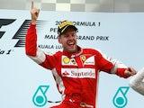Ferrari's Sebastian Vettel celebrates on the podium after winning the Malaysian Grand Prix on March 29, 2015
