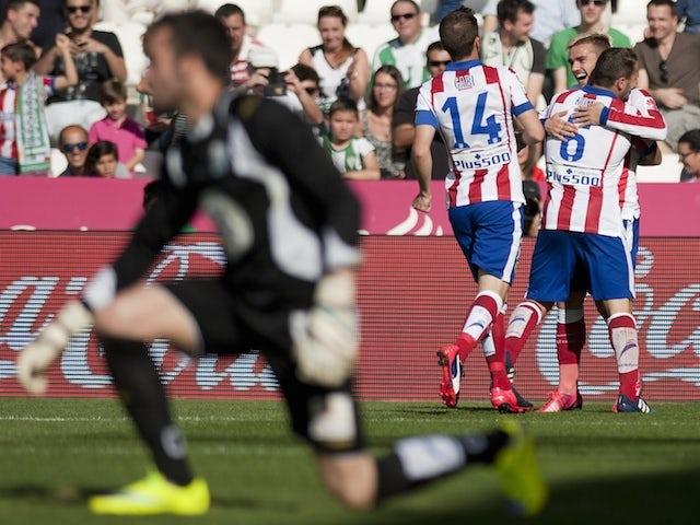 Atletico Madrid's French forward Antoine Griezmann (backR) celebrates after scoring with his teammates during the Spanish league football match Cordoba CF vs Club Atletico de Madrid at El Nuevo Arcangel stadium in Cordoba on April 4, 2015