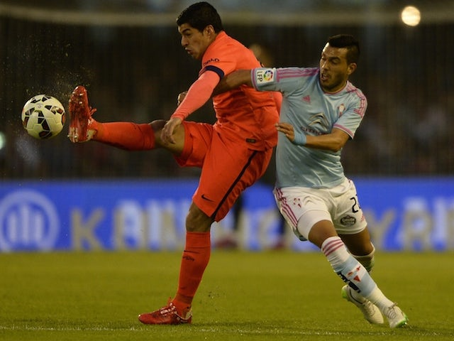 Celta's Argentinian defender Gustavo Cabral (R) vies with Barcelona's Uruguayan forward Luis Suarez during the Spanish league football match RC Celta de Vigo vs FC Barcelona at the Balaidos stadium in Vigo on April 5, 2015
