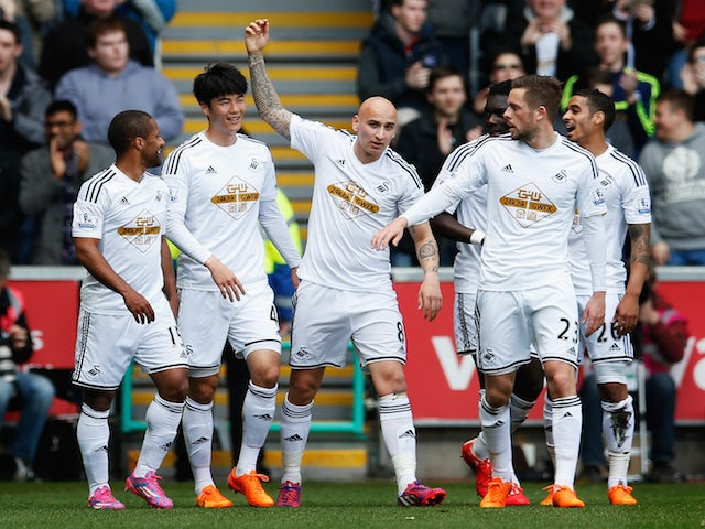 Ki Sung-Yueng of Swansea City celebrates scoring the opening goal with team mates during the Barclays Premier League match between Swansea City and Hull City at Liberty Stadium on April 4, 2015