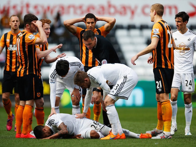 Referee Andre Marriner checks on Kyle Naughton of Swansea City after showing the red card to David Meyler of Hull City during the Barclays Premier League match between Swansea City and Hull City at Liberty Stadium on April 4, 2015