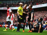 Jordan Henderson of Liverpool and Lucas Leiva of Liverpool argue with referee Anthony Taylor as Emre Can of Liverpool sits on the turf during the Barclays Premier League match between Arsenal and Liverpool at Emirates Stadium on April 4, 2015