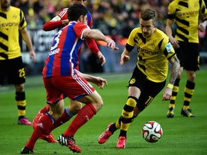 Bayern Munich's Spanish midfielder Xabi Alonso and Dortmund's striker Marco Reus (R) vie for the ball during the German first division Bundesliga football match Borussia Dortmund vs FC Bayern Munich in Dortmund, western Germany, on April 4, 2015