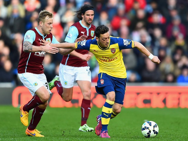 Mesut Ozil of Arsenal holds off Scott Arfield of Burnley during the Barclays Premier League match between Burnley and Arsenal at Turf Moor on April 11, 2015