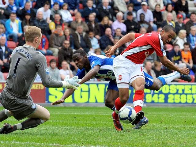 Arsenal's English forward Theo Walcott scores the opening goal past Wigan Athletic's English goalkeeper Chris Kirkland during the English Premier league football match at the DW Stadium, Wigan, north-west, England on April 18, 2010