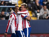 Atletico Madrid's French forward Antoine Griezmann celebrates with his teammates after scoring during the Spanish league football match Malaga CF vs Club Atletico de Madrid at La Rosaleda stadium in Malaga on April 11, 2015