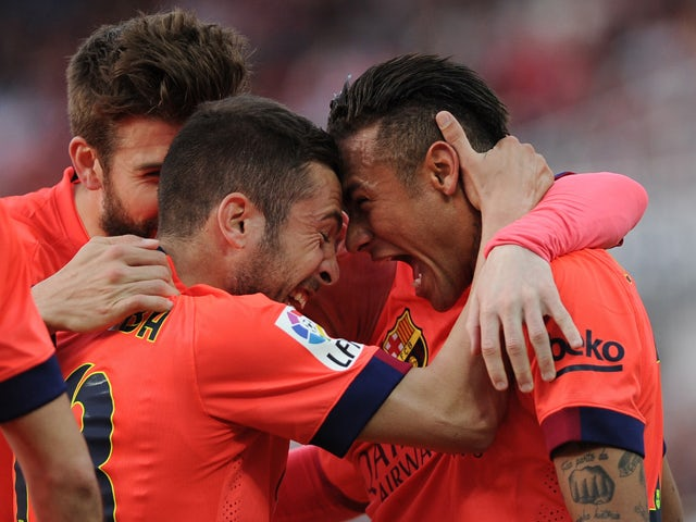 Barcelona's Brazilian forward Neymar celebrateswith Barcelona's defender Jordi Alba (L) after scoring during the Spanish league football match Sevilla FC vs FC Barcelona at the Ramon Sanchez Pizjuan stadium in Sevilla on April 11, 2015