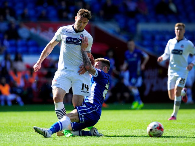 Bolton player Dorian Dervitte is challenged by Joe Ralls of Cardiff during the Sky Bet Championship match between Cardiff City and Bolton Wanderers at Cardiff City Stadium on April 6, 2015