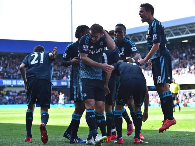 Chelsea's Serbian defender Branislav Ivanovic reacts to being hit by a coin as Chelsea players celebrate their goal during the English Premier League football match between Queens Park Rangers and Chelsea at Loftus Road Stadium in London on April 12, 2015