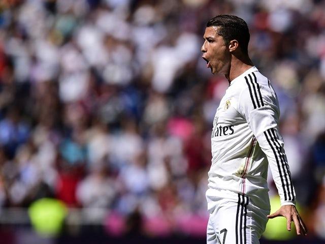 Real Madrid's Portuguese forward Cristiano Ronaldo celebrates after scoring a goal during the Spanish league football match Real Madrid CF vs SD Eibar at the Santiago Bernabeu stadium in Madrid on April 11, 2015.