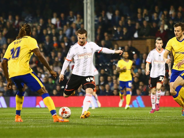 Ross McCormack of Fulham shoots past the Wigan Athletic defence to score their first goal during the Sky Bet Championship match between Fulham and Wigan Athletic at Craven Cottage on April 10, 2015