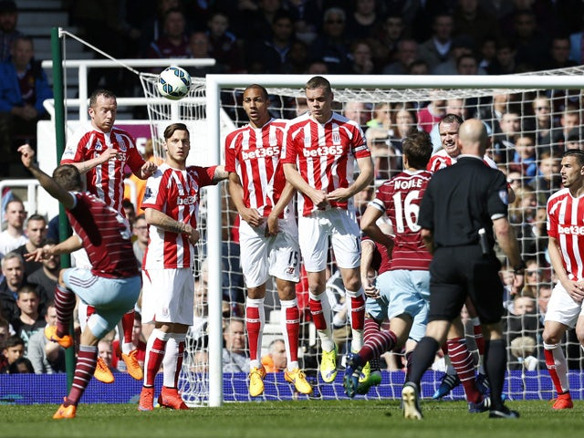 West Ham United's English defender Aaron Cresswell scores from this free kick during the English Premier League football match between West Ham United and Stoke City at Upton Park in London on April 11, 2015