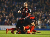 Yann Kermorgant of Bournemouth (obscured) is mobbed by team mates in celebration as he scores their first goal from a free kick during the Sky Bet Championship match between Brighton & Hove Albion and AFC Bournemouth at Amex Stadium on April 10, 2015