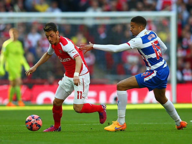Mesut Ozil of Arsenal is marshalled by Michael Hector of Reading during the FA Cup Semi Final between Arsenal and Reading at Wembley Stadium on April 18, 2015