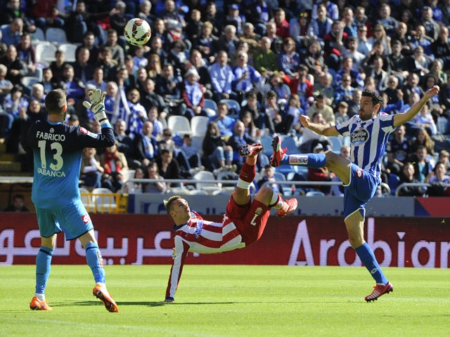 Atletico Madrid's French forward Antoine Griezmann kicks the ball over Deportivo's goalkeeper Fabri (L) and forward Toche to score a goal during the Spanish league football match RC Deportivo La Coruna v Club Atletico de Madrid at the Municipal de Riazor