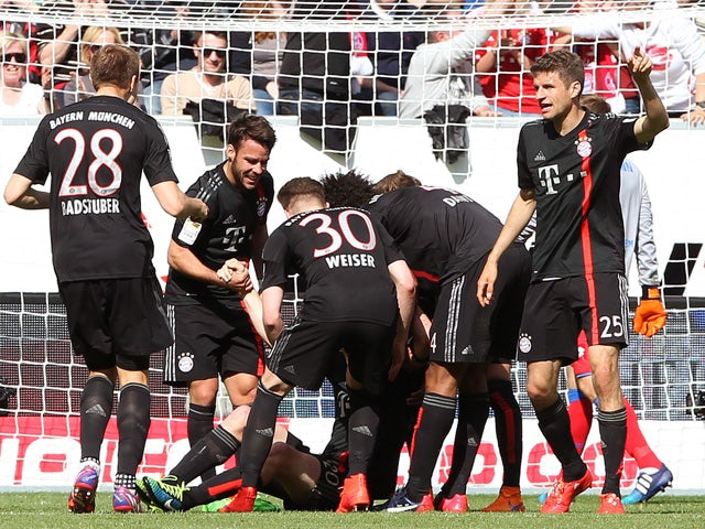Bayern Munich's midfielder Sebastian Rode celebrates with teammates after scoring the 0-1 during the German first division Bundesliga football match 1899 Hoffenheim vs FC Bayern Munich in Sinsheim, southern Germany, on April 18, 2015