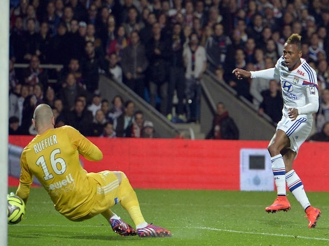 Lyon's Cameroonian forward Clinton Njie (R) shoots and scores a goal during the French L1 football match between Lyon and Saint-Etienne on April 19, 2015