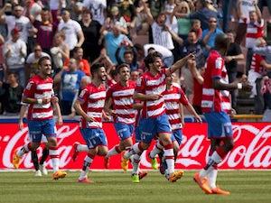 Granada's defender Diego Mainz celebrates with teammates after scoring a goal during the Spanish league football match Granada FC v Sevilla FC at Nuevo Los Carmenes stadium in Granada on April 19, 2015